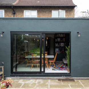 Mid-sized eclectic green one-story concrete exterior home photo in London with a green roof