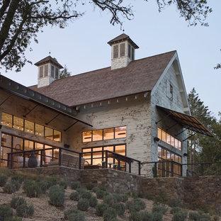 Foto de fachada blanca, industrial, grande, de una planta, con revestimiento de madera y tejado a dos aguas