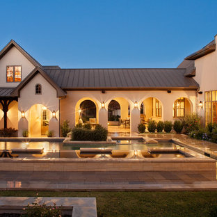 Tuscan beige two-story exterior home photo in Austin with a metal roof