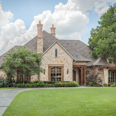 Large traditional beige one-story stone house exterior idea in Dallas with a hip roof and a shingle roof