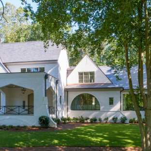 This is an example of an expansive transitional two-storey white house exterior in Atlanta with a gable roof and a tile roof.