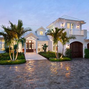 Ejemplo de fachada de casa blanca, marinera, grande, de dos plantas, con revestimiento de estuco, tejado a cuatro aguas y tejado de metal