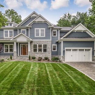 Imagen de fachada de casa azul, de estilo americano, grande, de tres plantas, con revestimiento de aglomerado de cemento, tejado de teja de madera y tejado a dos aguas