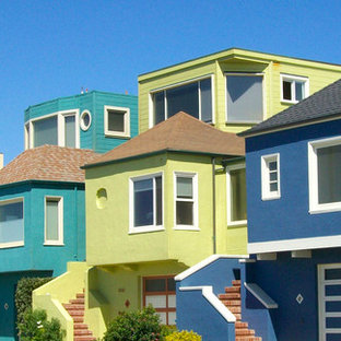 Exempel på ett mellanstort eklektiskt flerfärgat hus, med tre eller fler plan, stuckatur och valmat tak