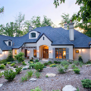 Mid-sized french country beige one-story stucco exterior home idea in Other with a hip roof