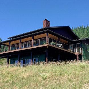 Modelo de fachada de casa verde, clásica, grande, de dos plantas, con revestimientos combinados, tejado a dos aguas y tejado de teja de madera