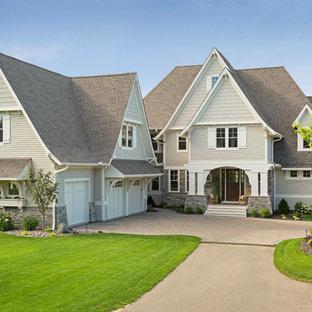 Imagen de fachada beige, de estilo americano, extra grande, de tres plantas, con revestimiento de vinilo
