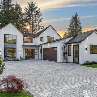 Ejemplo de fachada blanca, de estilo de casa de campo, grande, de dos plantas, con revestimiento de estuco, tejado a dos aguas y tejado de teja de madera