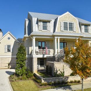 Modelo de fachada de casa beige, marinera, grande, de tres plantas, con revestimiento de madera, tejado a doble faldón y tejado de metal