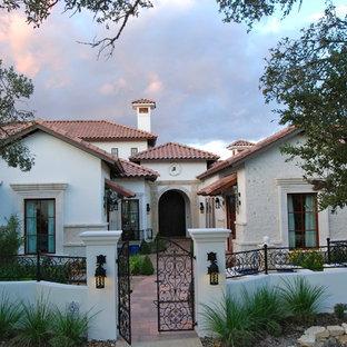 Foto de fachada de casa beige, mediterránea, extra grande, de dos plantas, con revestimiento de estuco, tejado a cuatro aguas y tejado de teja de barro