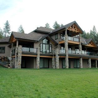 Ejemplo de fachada gris, moderna, grande, de tres plantas, con revestimiento de madera y tejado a la holandesa
