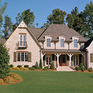 Photo of a large transitional two-storey brick red house exterior in Other with a clipped gable roof and a shingle roof.