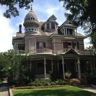Aménagement d'une grand façade en bois rose victorienne à deux étages et plus avec un toit à quatre pans.