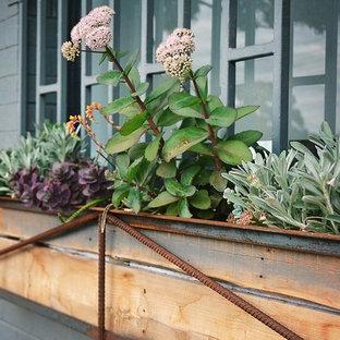 Foto de fachada de casa gris, industrial, pequeña, de una planta, con revestimiento de ladrillo, tejado a dos aguas y tejado de teja de barro