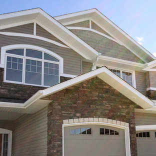 Example of a classic beige split-level stone exterior home design in Calgary