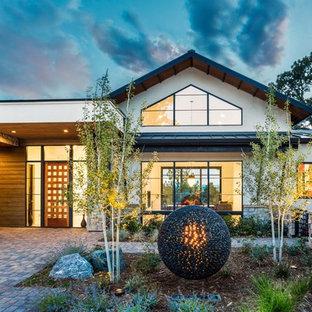 Immagine della facciata di una casa unifamiliare ampia multicolore contemporanea a due piani con rivestimenti misti, tetto a capanna e copertura in metallo o lamiera