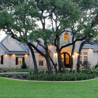 Huge traditional white two-story stone exterior home idea in Austin