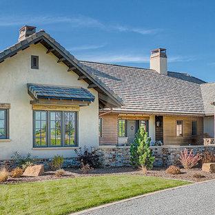 Diseño de fachada beige, rústica, grande, de una planta, con revestimiento de adobe