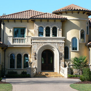 Inspiration för ett stort medelhavsstil hus, med två våningar och valmat tak