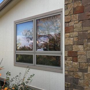 Diseño de fachada de casa beige, vintage, grande, a niveles, con revestimientos combinados