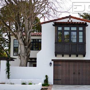 Modelo de fachada blanca, mediterránea, grande, de dos plantas, con revestimiento de estuco