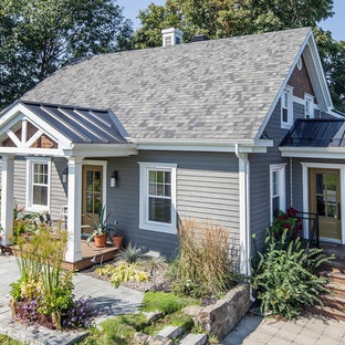 Example of a cottage chic gray two-story mixed siding gable roof design in Montreal