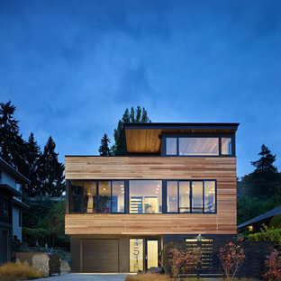 Foto de fachada negra, contemporánea, de tamaño medio, de tres plantas, con revestimiento de madera y tejado plano
