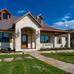 Elegant beige two-story stone exterior home photo in Austin with a metal roof