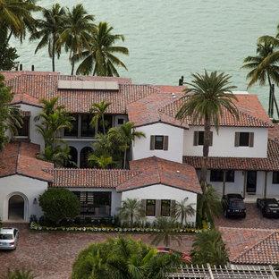 Diseño de fachada blanca, tropical, de dos plantas, con revestimiento de estuco y tejado a cuatro aguas