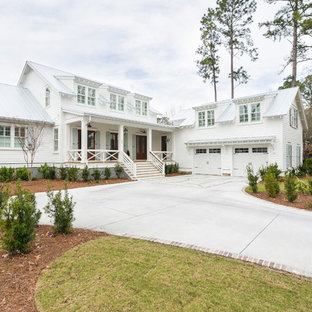 Esempio della facciata di una casa unifamiliare bianca country a due piani con tetto a capanna, copertura in metallo o lamiera e rivestimento in legno