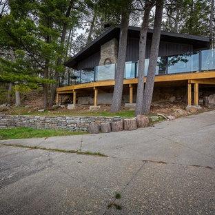Foto de fachada de casa gris, romántica, de tamaño medio, a niveles, con revestimiento de madera, tejado a dos aguas y tejado de metal