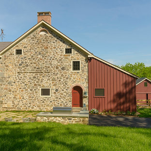 Country red three-story stone gable roof idea in Philadelphia