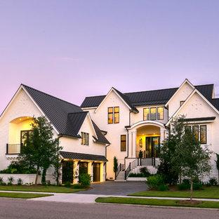 Diseño de fachada de casa blanca, clásica renovada, de dos plantas, con revestimiento de ladrillo, tejado a dos aguas y tejado de metal