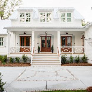 Immagine della facciata di una casa unifamiliare bianca country a due piani con rivestimento in legno, copertura in metallo o lamiera e tetto bianco