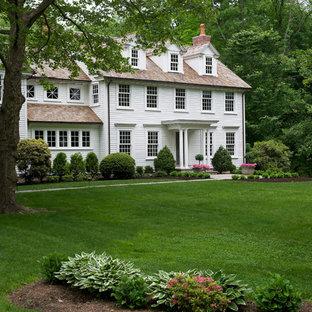 Идея дизайна: большой, трехэтажный, белый дом в классическом стиле с облицовкой из винила и двускатной крышей