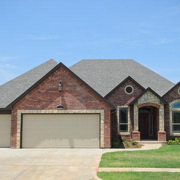 Dark Red Brick Home with Stone Around Windows and Garage