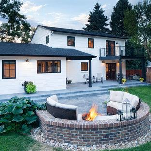 Foto de fachada de casa blanca, campestre, de dos plantas, con revestimiento de aglomerado de cemento, tejado a dos aguas y tejado de teja de madera