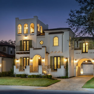 This is an example of a beige mediterranean detached house in Tampa with three floors, a hip roof and a tiled roof.