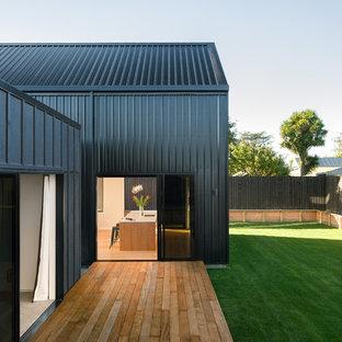 Imagen de fachada de casa pareada negra, costera, pequeña, de dos plantas, con revestimiento de madera, tejado a dos aguas y tejado de metal