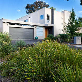 Mid-sized contemporary beige two-story exterior home idea in Canberra - Queanbeyan with a metal roof