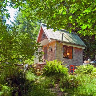 Esempio della facciata di una casa piccola rustica a un piano con rivestimento in legno e tetto a capanna
