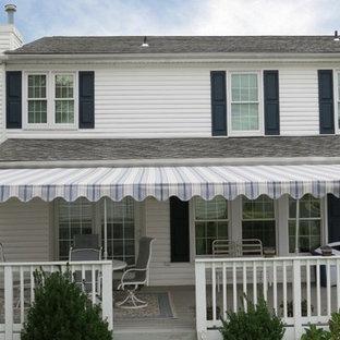 Ejemplo de fachada de casa blanca, retro, grande, de dos plantas, con revestimiento de vinilo, tejado a la holandesa y tejado de teja de madera