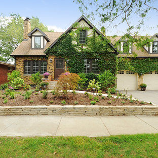 Example of a cottage beige two-story brick exterior home design in Chicago