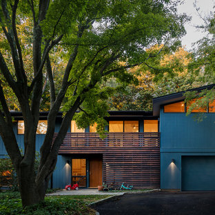 Example of a mid-sized mid-century modern blue two-story wood house exterior design in New York with a shed roof