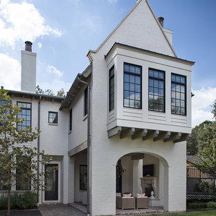 Ejemplo de fachada blanca, tradicional, con revestimiento de ladrillo y tejado a dos aguas