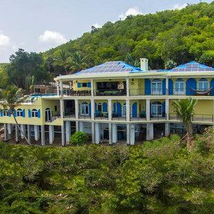 Immagine della facciata di una casa unifamiliare ampia gialla tropicale a due piani con rivestimento in cemento, tetto a una falda e copertura in metallo o lamiera