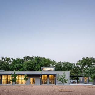 Imagen de fachada gris, urbana, grande, de una planta, con revestimiento de metal y tejado a dos aguas