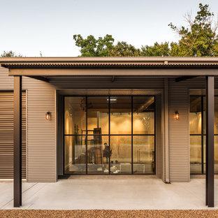Modelo de fachada gris, urbana, grande, de una planta, con revestimiento de metal y tejado a dos aguas