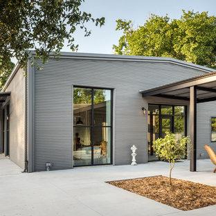 На фото: большой, одноэтажный, серый дом в стиле лофт с облицовкой из металла и двускатной крышей с