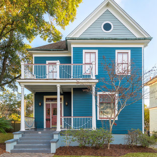 Large ornate blue wood exterior home photo in Other with a shingle roof